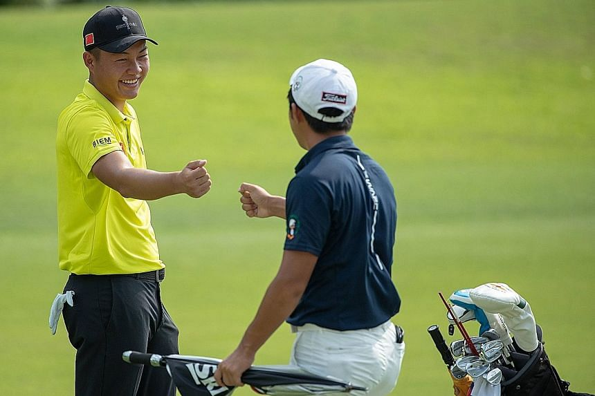 A good shot by Chinese golfer Lin Yuxin during his round of 62 is acknowledged by flight-mate Takumi Kanaya.