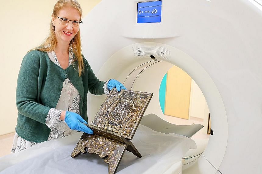 Ms Birte Koehler, a senior object conservator at the Heritage Conservation Centre, with a centuries-old wooden book stand that underwent a CT scan at the Singapore General Hospital yesterday.