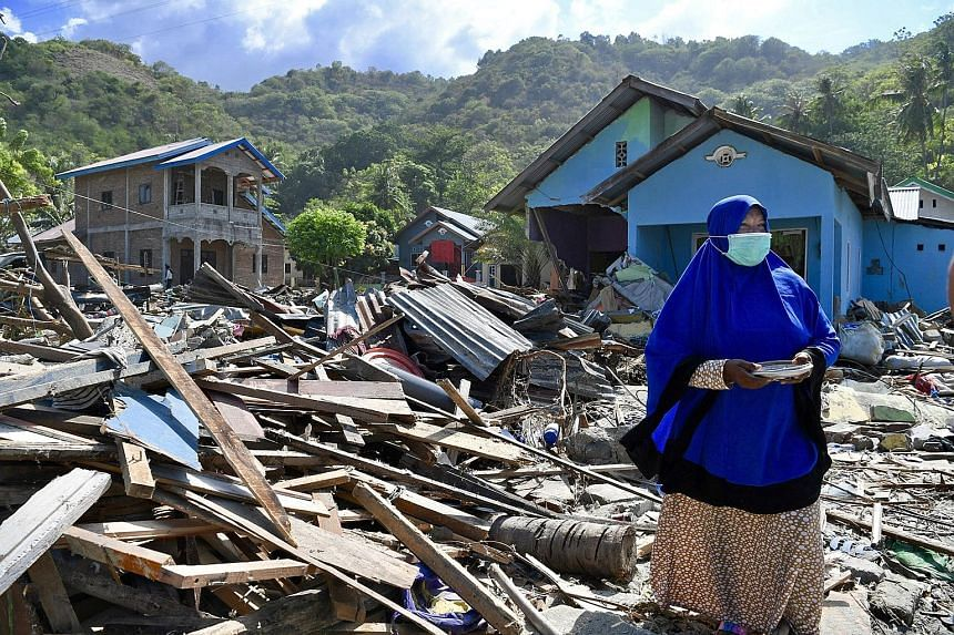 Ms Ipa Thamrin scavenging for scrap metal in front of her house which was destroyed by the 7.4 magnitude earthquake and tsunami. Children hit by the catastrophe begging for help or donations (above) from passing motorists along the road leading to Pa