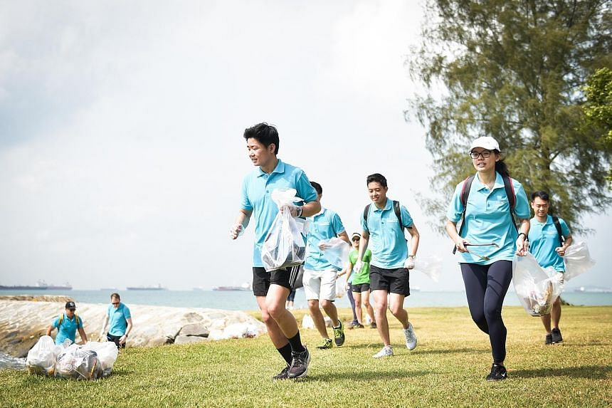 """Mr Lee Leong Hui (in front) plogging at the East Coast beach with his colleagues from property firm Lendlease last Thursday, as part of the company's annual community day. The term """"plogging"""" is a mash-up of the word """"jogging"""" and the Swedish words """""""