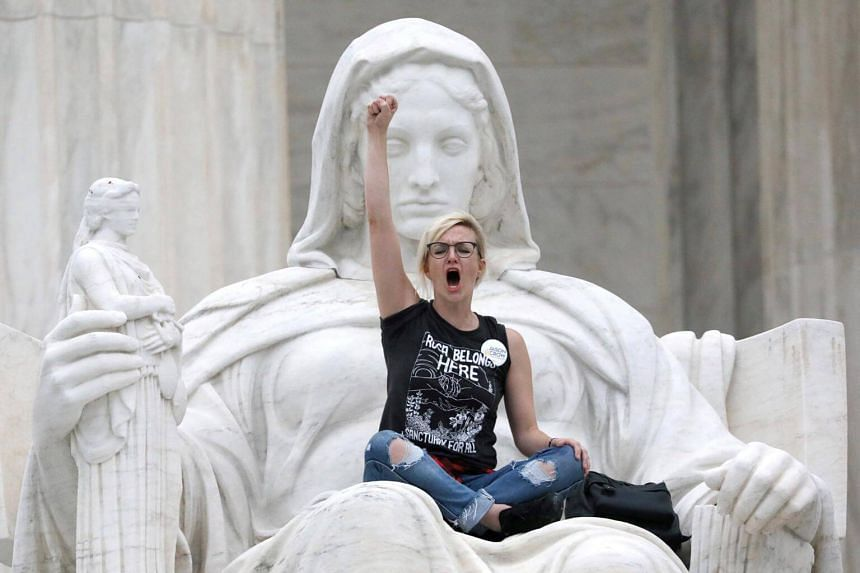 A protester sits on the lap of the Lady Justice statue on the steps of the US Supreme Court, in Washington, US, on Oct 6, 2018.