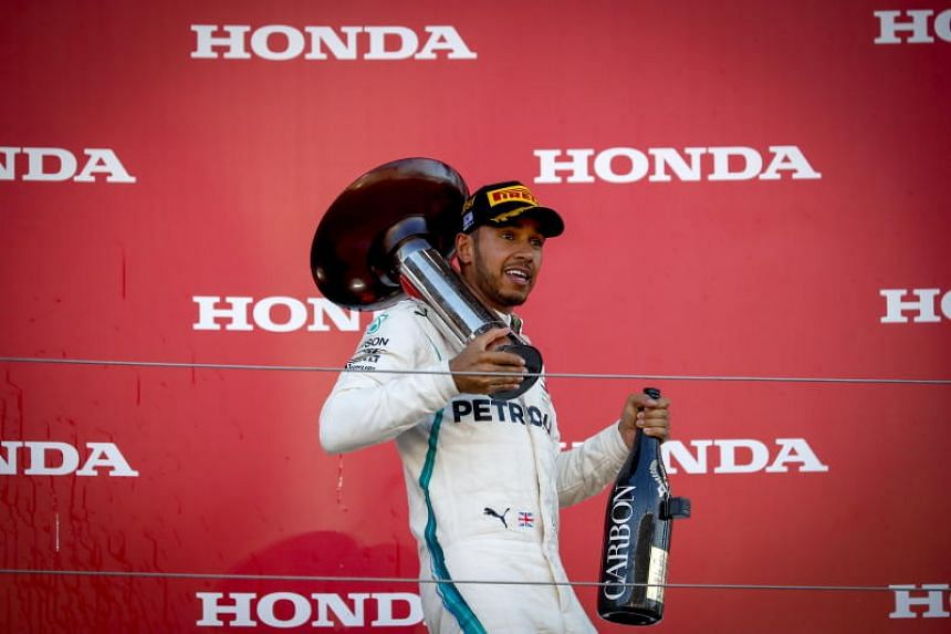 Formula One driver Lewis Hamilton carries his trophy on the podium after winning the Japanese Formula One Grand Prix at the Suzuka Circuit in Suzuka, Japan, on Oct 7, 2018.