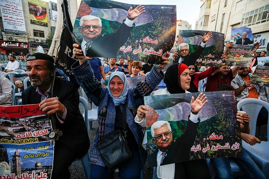 Palestinians chanting slogans and waving pictures of President Mahmoud Abbas during a demonstration in the West Bank city of Ramallah on Sept 27, ahead of his speech during the General Debate of the 73rd session of the General Assembly at the United