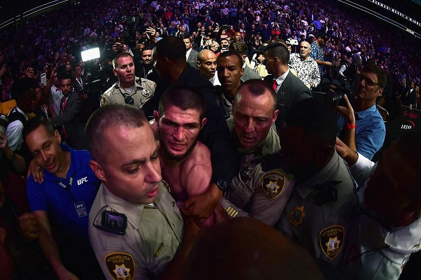 Above: Khabib Nurmagomedov's choke on Conor McGregor saw the Irishman tap out in the fourth round. Left: Nurmagomedov is escorted out of the arena. He is expected to be heavily disciplined by the Nevada State Athletic Commission, which is withholding