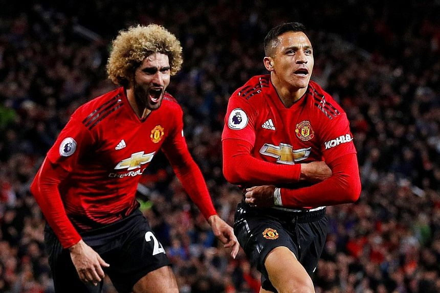 Alexis Sanchez feels tempted to pull off his jersey as he runs off in celebration of his 90th-minute winning goal against Newcastle, with teammate Marouane Fellaini in pursuit.