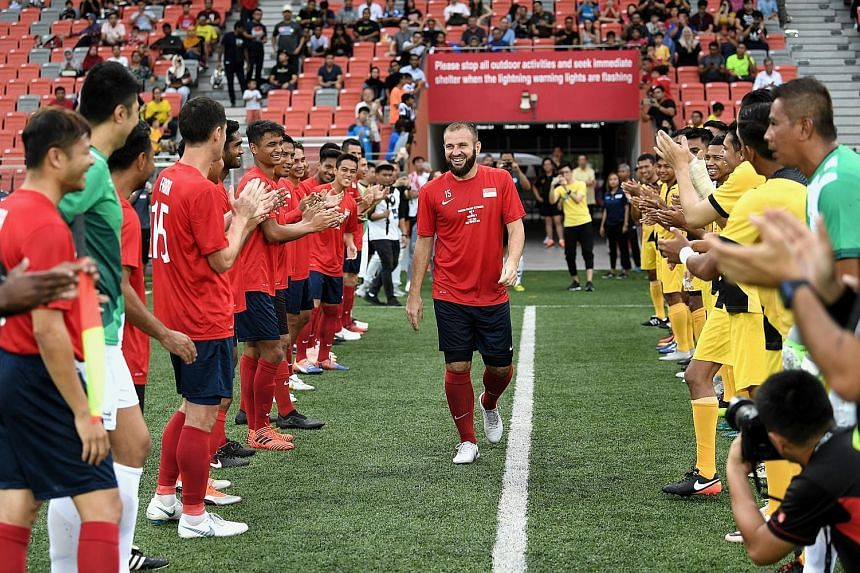 A Singapore All-Stars team and a Tampines Rovers All-Stars team form a guard of honour in welcoming Fahrudin Mustafic onto the field for his testimonial match at Our Tampines Hub last night. He played for Singapore 87 times, scoring eight goals for t