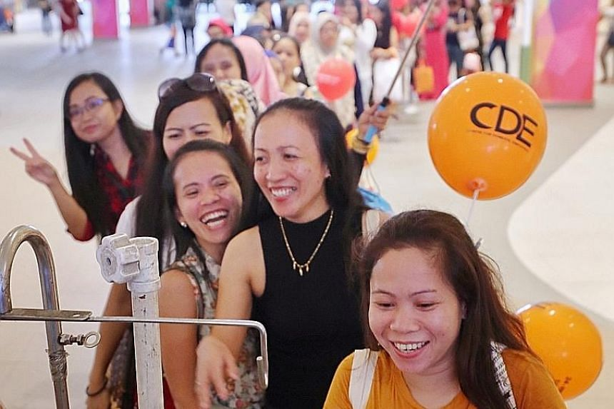 Maids queueing for free ice cream at an event at Heartbeat@ Bedok organised by the Centre for Domestic Employees yesterday. The Manpower Ministry said the practice of employers safekeeping the money of maids poses inconveniences and risks to both par