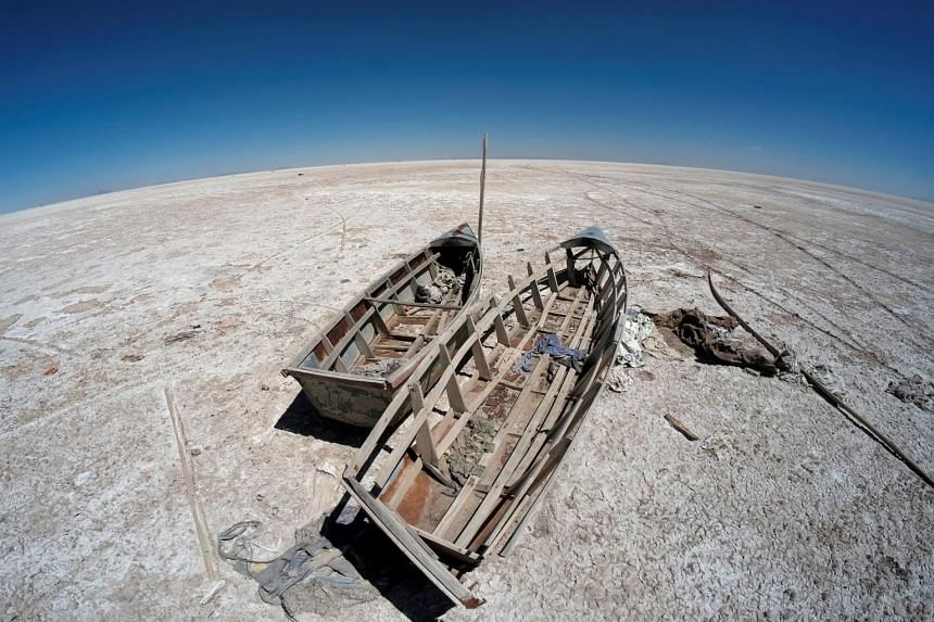Boats are seen on the dried lake Poopo affected by climate change, in Bolivia, on Sept 1, 2017.