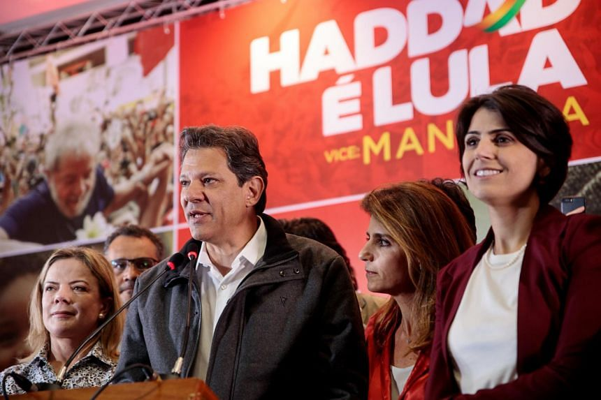 Mr Fernando Haddad, presidential candidate for the Workers' Party, speaks as his wife Ana Estela Haddad (third from left) looks on.