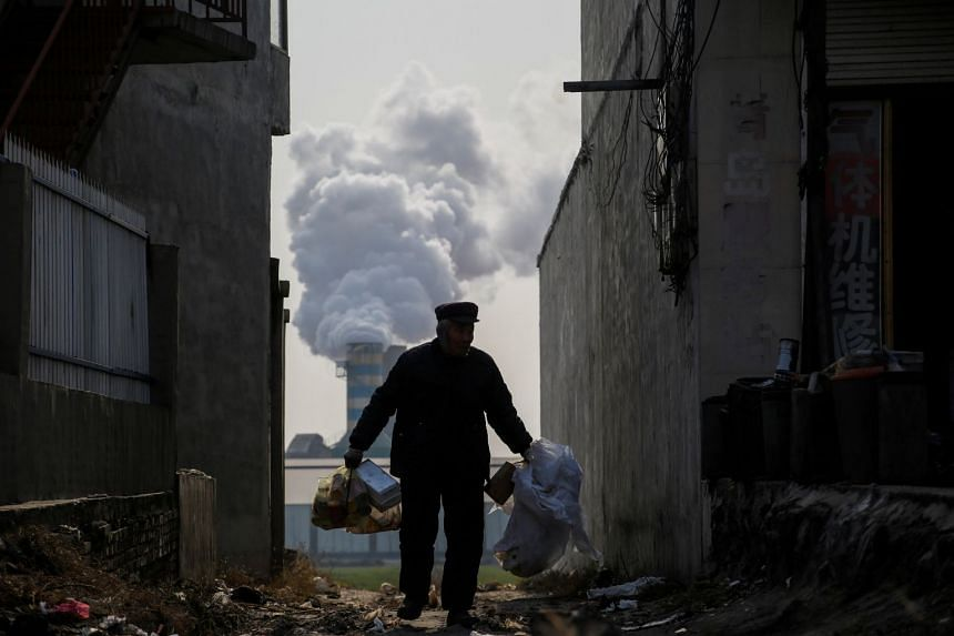 A man collecting recyclables from an alley as smoke billows from the chimney of a factory in rural Gaoyi county, China, on Dec 7, 2017.