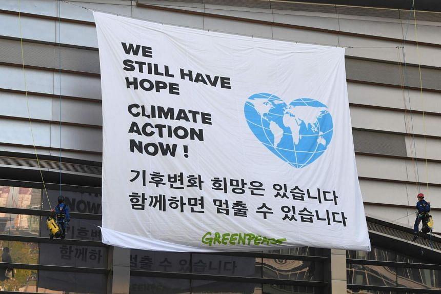 Greenpeace activists display a banner during an activity prior to a press conference of the Intergovernmental Panel for Climate Change at Songdo Convensia in Incheon, on Oct 8, 2018.