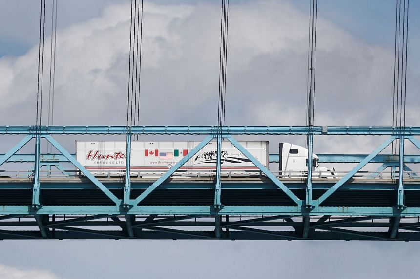 A commercial truck with a Canada, United States and Mexico flag on its side is seen crossing over the Ambassador Bridge into Windsor, Ontario, from Detroit, Michigan, on Aug 29, 2018.