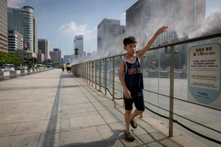 A child walks past a misting fountain in the central Gwanghwamun area of Seoul, on Aug 1, 2018. The world has already warmed about 1 deg C since pre-industrial times, fuelling stronger storms, more extreme floods, deadlier heatwaves and wildfires.