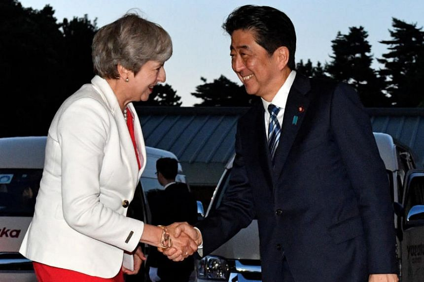 British Prime Minister Theresa May is welcomed by Japanese Prime Minister Shinzo Abe upon her arrival for a Japan-UK dinner at the Kyoto State Guest House in Kyoto, Japan, on Aug 30, 2017.