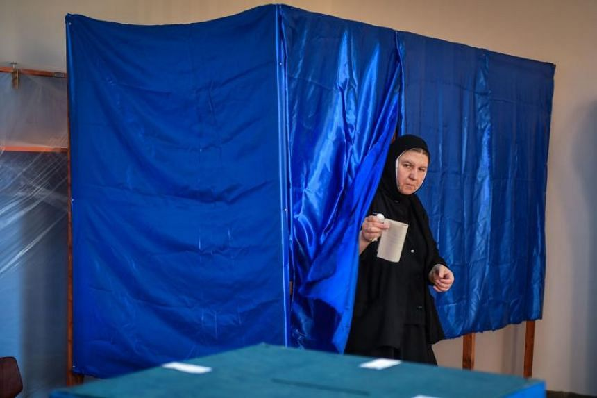 """A Romanian Christian-Orthodox nun votes at a polling station in the village of Branesti, Romania, in a referendum to change the constitutional definition of """"family"""", on Oct 6, 2018."""
