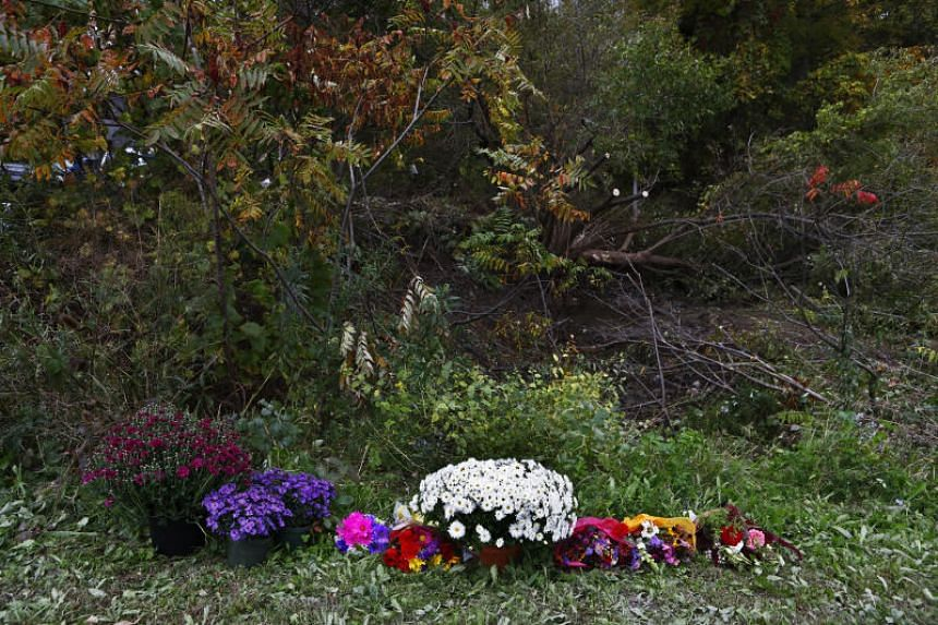 Flowers are left at the spotwhere a limousine crashed near the Apple Barrel Country Store in Schoharie, New York, on Oct 7, 2018.