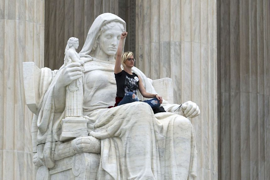 Protester Jessica Campbell-Swanson raising a defiant fist while seated on the lap of the Contemplation of Justice statue outside the Supreme Court in Washington on Saturday. Many chanted and waved anti-Kavanaugh placards as police officers pushed the