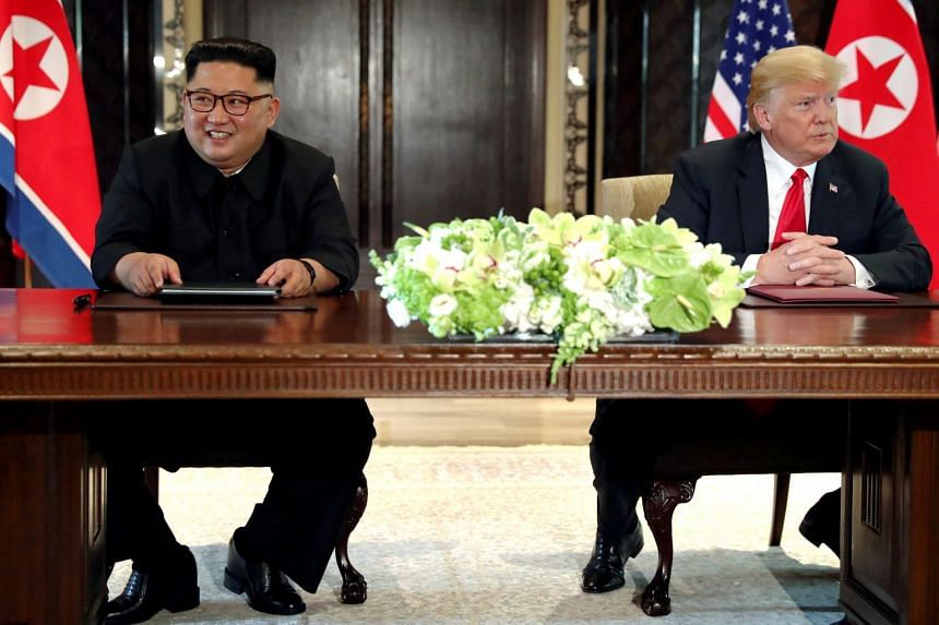 Mr Trump and Mr Kim hold a signing ceremony at the conclusion of their June 2018 summit in Singapore.