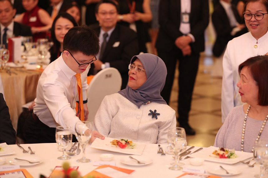 Johannes Cheong Hui Ming serves the first dinner course to President Halimah Yacob. Selected youths from the Hi-Job! Programme showed their appreciation by serving food at the President's table at the event.