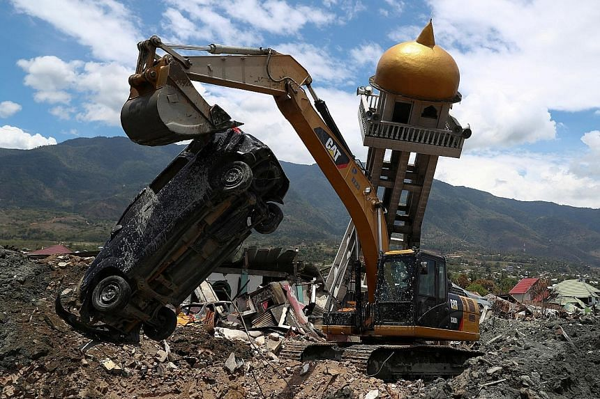 An excavator removing a damaged car yesterday from among the debris caused by the recent earthquake in Palu, in Indonesia's Central Sulawesi province.