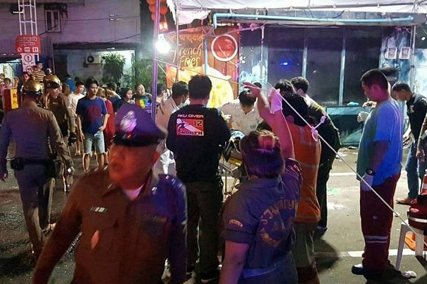 The scene of the deadly skirmish on Sunday (above) in central Bangkok's Pratunam district, which left one man dead and four others injured. Officers (left) were spotted at work in the area the following day.