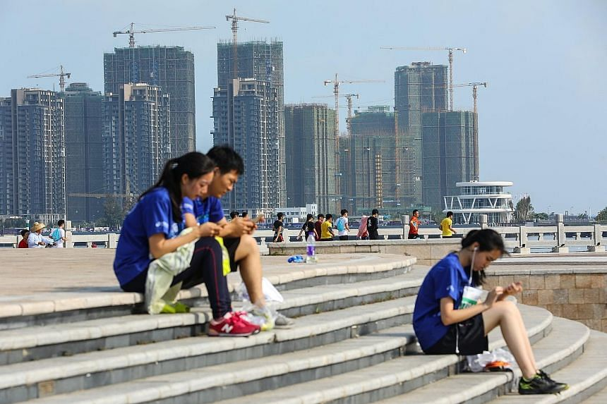Residential buildings under construction in Haikou in China's Hainan province. Home buyers angry that apartments are being sold for much less than what they paid swarmed property developers' marketing offices across the country over the Golden Week h
