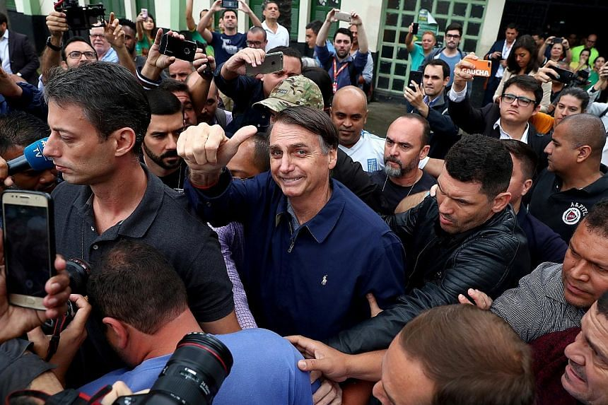Mr Jair Bolsonaro of the Social Liberal Party gesturing on Sunday after casting his vote in Rio de Janeiro. He has portrayed himself as the only candidate untainted by corruption.
