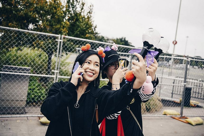 Fans arming themselves with light sticks - called Army bombs - before a concert by K-pop boyband BTS in New York last Saturday.