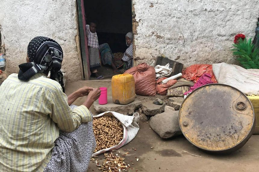 A woman prepares groundnuts outside her home in a neighbourhood in Harar, Ethiopia, on July 22, 2018.