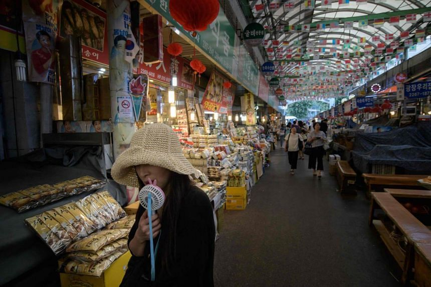 A woman uses an electric fan as she walks through a market in Seoul, on Aug 1, 2018.