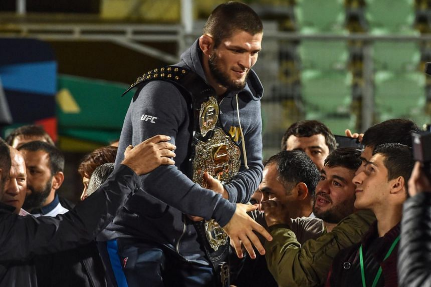 UFC lightweight champion Khabib Nurmagomedov carrying his champions belt as he is escorted by fans upon arrival in Makhachkala, Russia, on Oct 8, 2018.