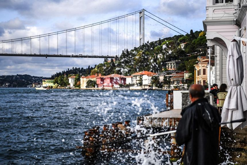 A fisherman works beside waterside mansions on the Bosphorus River coast in Istanbul on Sept 28, 2018. Foreigners have been buying up the properties that were once the preserve of the Ottoman elite.