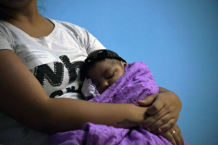 A woman holds her four-month-old baby, who was born with microcephaly, as they wait for medical exams in Rio de Janeiro, Brazil, on Jan 2, 2017.