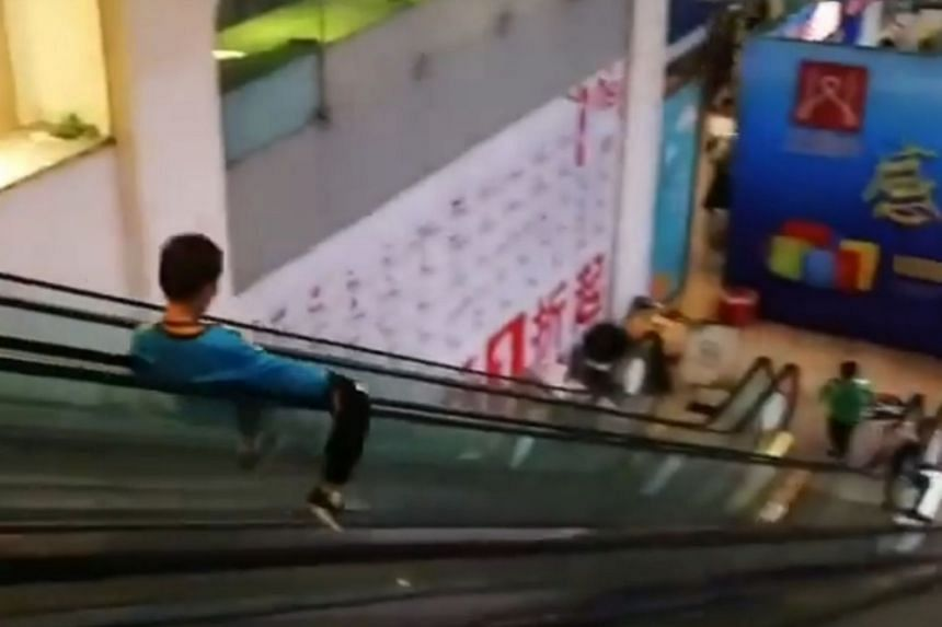 The boys took turns to slide down the escalator, which is about three storeys high, as the adults cheer them on.