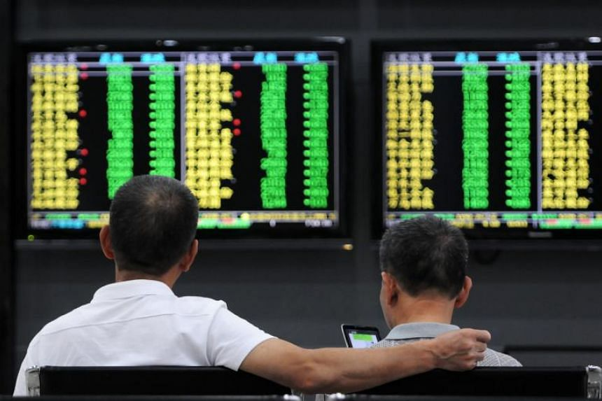 Investors monitor stock prices at a securities company in Jiujiang in China's central Jiangxi province, on Oct 8, 2018.
