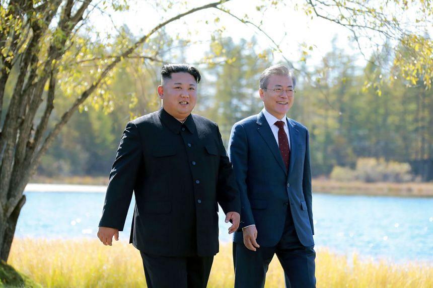 North Korean leader Kim Jong Un (left) and South Korean President Moon Jae-in walking together during a visit to Samjiyon guesthouse near Mount Paektu, on Sept 20, 2018.