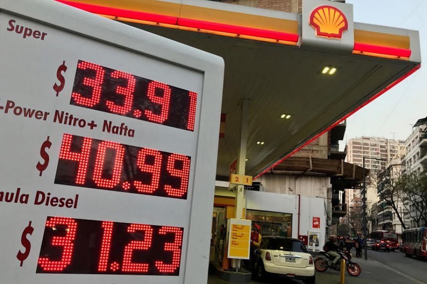 An employee pumps fuel as petrol prices are seen on a billboard at a Shell petrol station in Buenos Aires.