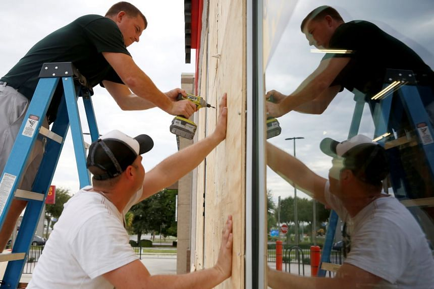 Justin Davis (left) and Brock Mclean board up a business in advance of Hurricane Michael in Destin, Florida, on Oct 9, 2018.