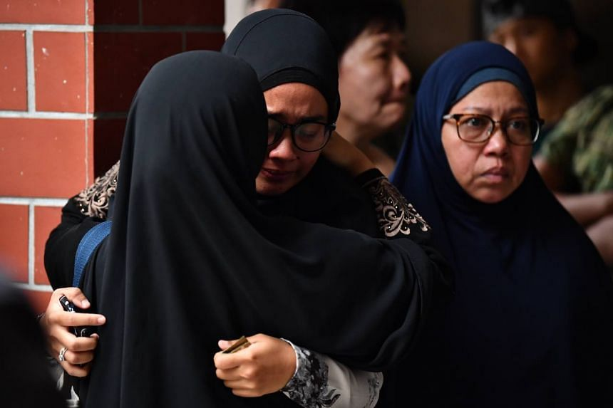 "Third Warrant Officer Muhammad Sadikin Hasban's wife Norsidah Kamilan (centre) told reporters she was ""not ready"" to talk."