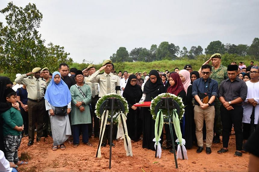 Colonel Andrew Lim (centre, in uniform), Commander of 9th Singapore Division and Chief Infantry Officer, salutes Third Warrant Officer Muhammad Sadikin Hasban during the burial.