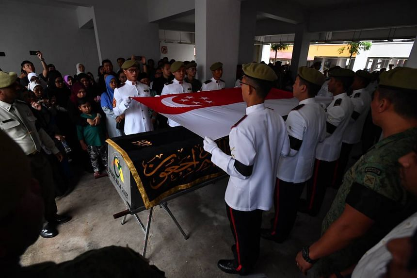 A Singapore flag being draped over Third Warrant Officer Muhammad Sadikin Hasban's coffin.