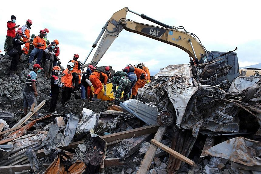 Rescue workers pulling a body yesterday from the rubble of a destroyed mosque at Balaroa neighbourhood in Palu. No one knows how many people are missing, especially in areas of southern Palu devastated by soil liquefaction.