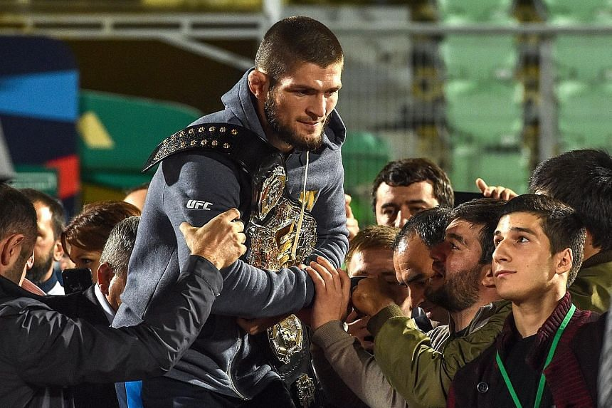 UFC lightweight champion Khabib Nurmagomedov carrying his champions' belt as he is escorted by fans upon arrival in Makhachkala, Dagestan, yesterday. The Russian defeated Conor McGregor of Ireland in their UFC lightweight championship bout by way of
