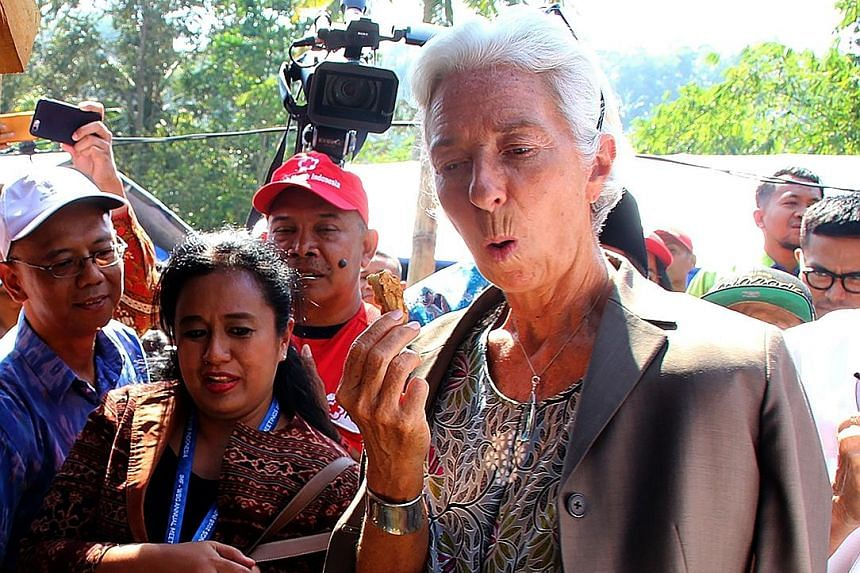 IMF chief Christine Lagarde sampling fried banana on a visit to Gunung Sari on Lombok Island on Monday. Supporters of presidential hopeful Prabowo Subianto have said the government was insensitive in going ahead with the meetings in the aftermath of