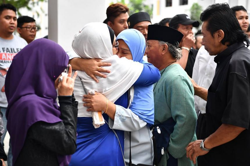 Friends and relatives offer comfort to Third Warrant Officer Muhammad Sadikin Hasban's parents Hasban Matman (in green) and Naisah Sepon (in blue tudung).