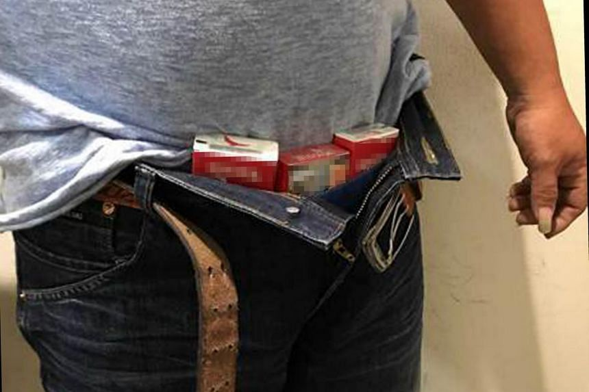 Officers found four packets of duty-unpaid cigarettes hidden under the man's clothes, along his waistline, and another packet in his bag.