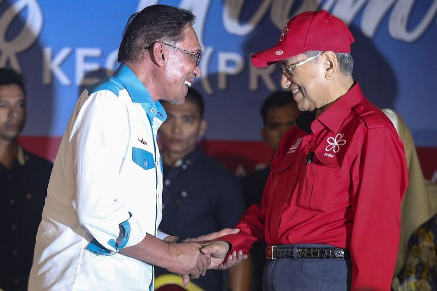 Anwar Ibrahim (left) and current Malaysian Prime Minister Mahathir Mohamad shake hands during a campaign ahead of the by-election in Port Dickson, Malaysia, on Oct 8, 2018.