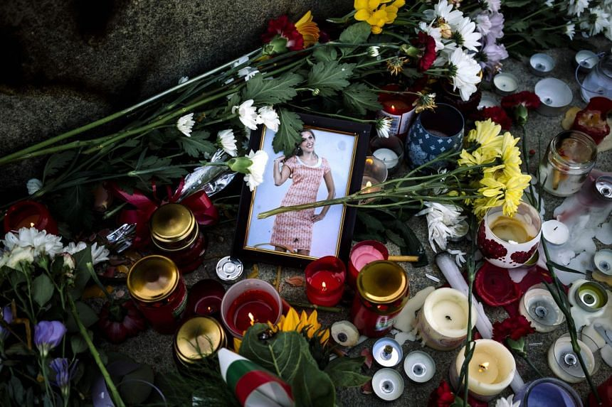 Flowers and candles are placed near a portrait of slain Bulgarian television journalist Viktoria Marinova in the city of Rousse, on Oct 9, 2018.