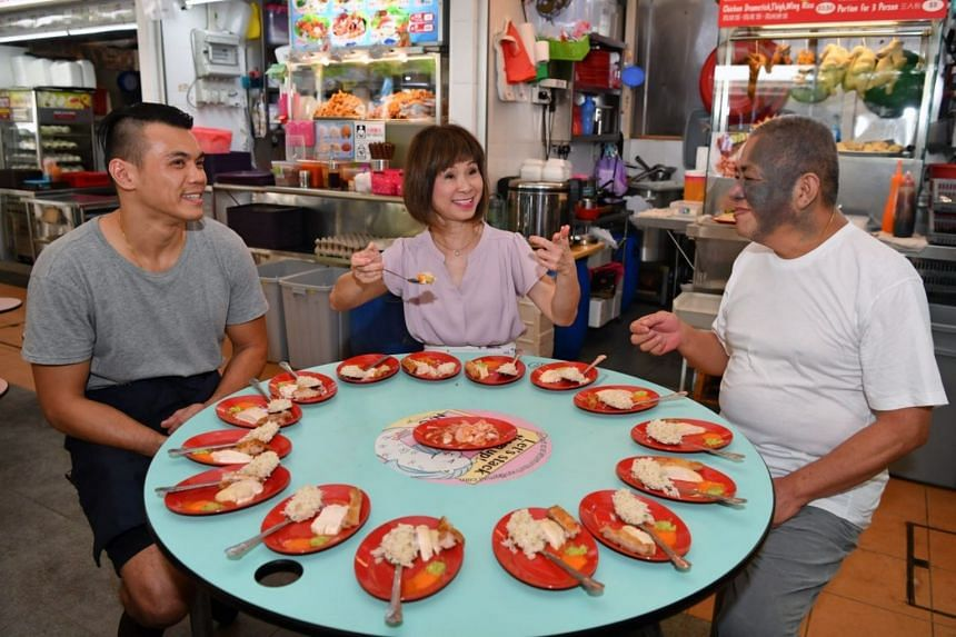 Senior Minister of State for the Environment and Water Resources Amy Khor trying the chicken rice prepared by hawkers Hoe Cherh Inn (left) of Ying's Hainanese Chicken Rice and Neo Cheng Leong.