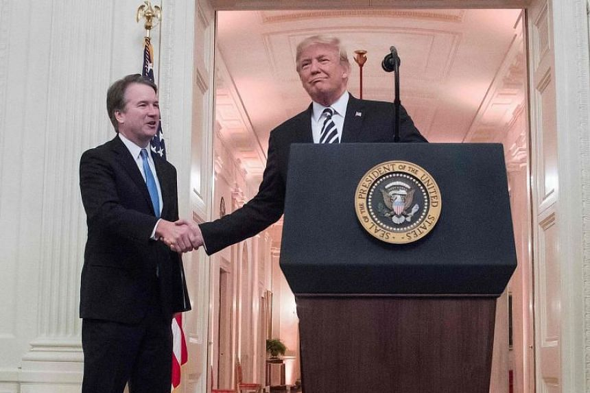 United States President Donald Trump (right) shakes hands with Judge Brett Kavanaugh at the White House in Washington, DC, on Oct 8, 2018.